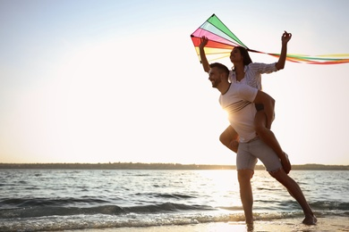 Happy couple playing with kite on beach near sea. Spending time in nature