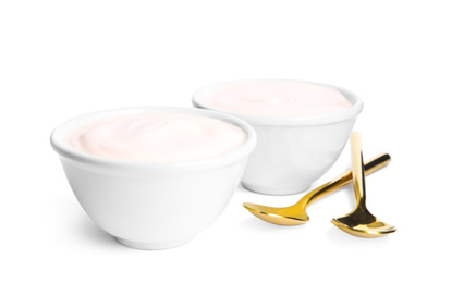 Tasty organic yogurt in bowls and spoons isolated on white