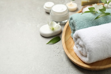Spa composition with towels and skin care products on grey textured table, space for text