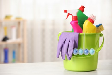 Different toilet cleaning supplies and tools in bucket on table indoors, space for text