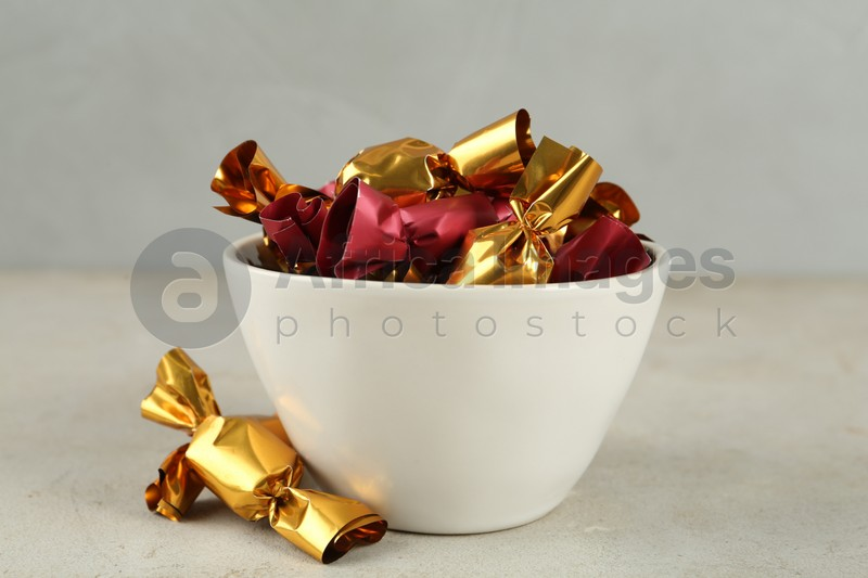 Candies in colorful wrappers on light beige table, closeup