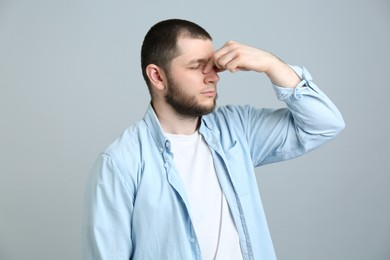 Man suffering from runny nose on light grey background