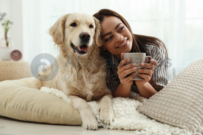 Young woman with cup of drink and her Golden Retriever at home. Adorable pet