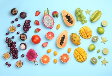 Many different delicious exotic fruits on light blue background, flat lay