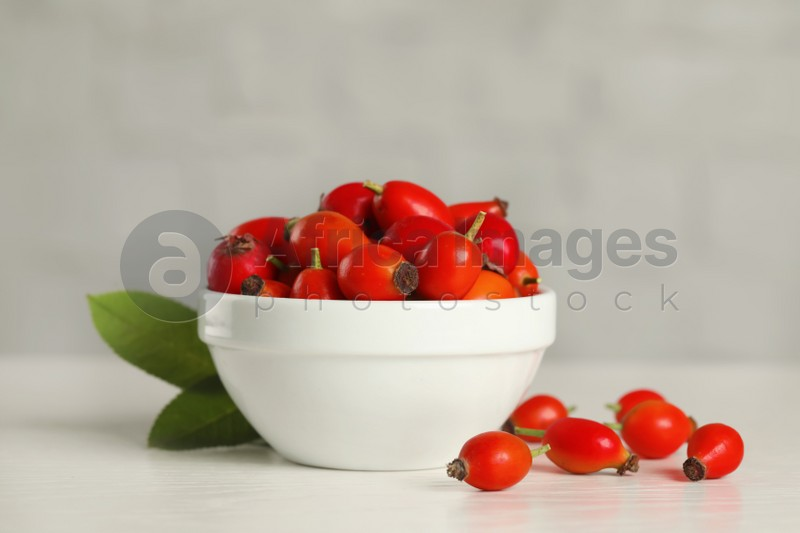 Ripe rose hip berries with green leaves on white wooden table