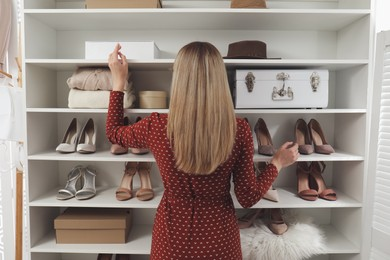 Young woman near shelving unit with shoes and accessories in dressing room, back view