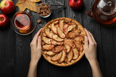Woman with delicious apple pie at black wooden table, top view