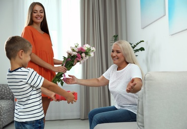 Mother and son congratulating mature woman at home