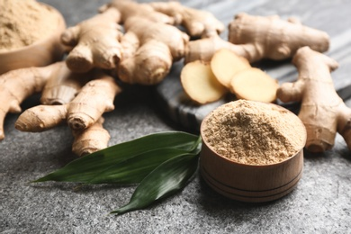 Dry ginger powder, fresh root and leaves on grey table