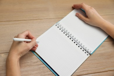 Left-handed woman writing in notebook at wooden table, closeup