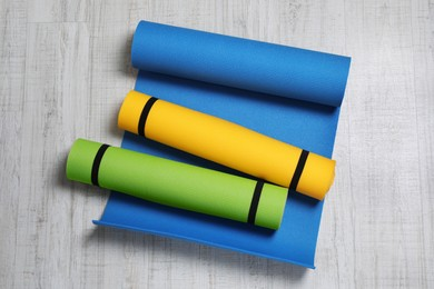 Bright camping mats on white wooden background, top view
