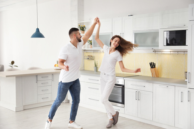 Lovely young couple dancing in kitchen at home