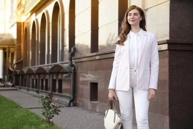 Young businesswoman near modern building on city street