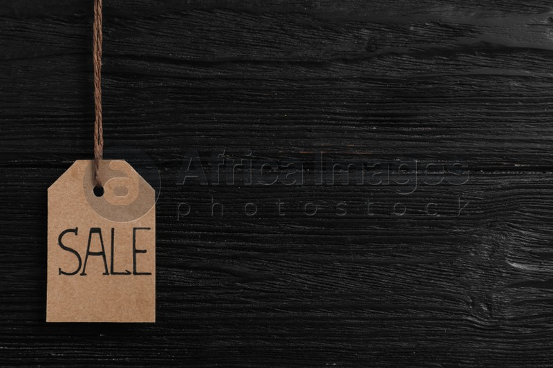 Sale tag on wooden background, space for text. Black Friday concept