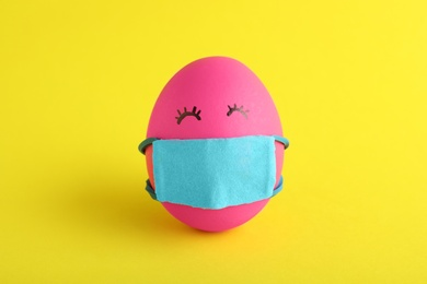 Bright egg in protective mask on yellow background. Easter holiday during coronavirus quarantine