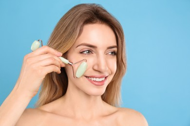 Young woman using natural jade face roller on light blue background
