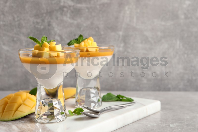 Delicious panna cotta with mango coulis served on light grey table. Space for text