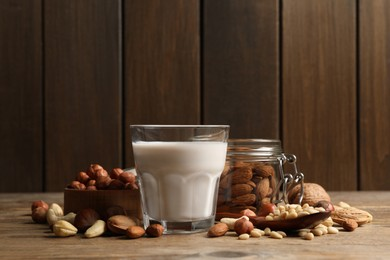 Vegan milk and different nuts on wooden table