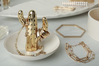 Decorative cactus with stylish golden bijouterie on white marble table, closeup