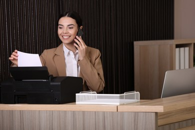 Receptionist talking on smartphone at countertop in office