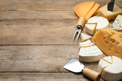 Set of different cheeses and specialized knives and fork on wooden table. Space for text