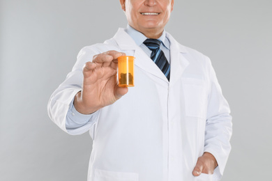 Senior pharmacist with pills on light grey background, closeup
