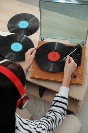Woman listening to music with turntable at home, above view