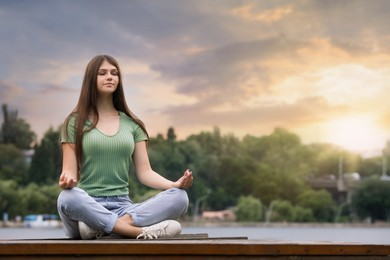 Teenage girl meditating near river. Space for text