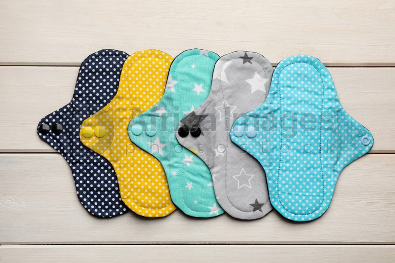Many reusable cloth menstrual pads on white wooden table, flat lay