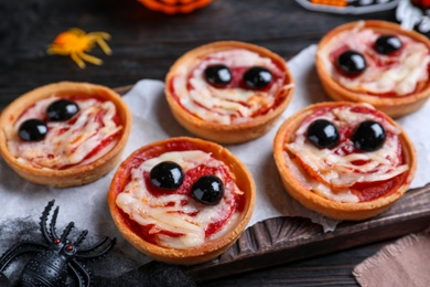 Cute monster tartlets served on black wooden table, closeup. Halloween party food