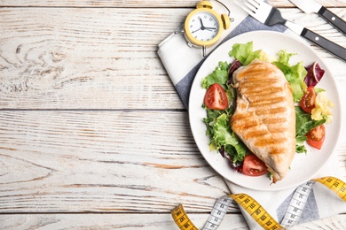 Plate of appetizing food, alarm clock and measuring tape on white wooden table, flat lay with space for text. Nutrition regime
