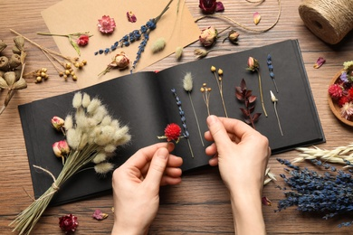 Woman making herbarium of dry flowers at wooden table, closeup