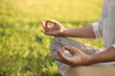 Man meditating outdoors on sunny day, closeup. Space for text