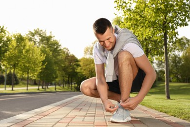 Young man tying laces of sneakers outdoors. Morning fitness