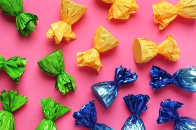 Candies in colorful wrappers on pink background, flat lay
