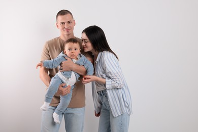 Portrait of happy family with little child on light background. Space for text