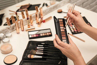 Professional makeup artist with eyeshadow palette  and brush at dressing table, closeup