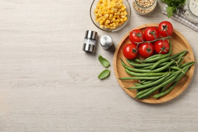 Fresh green beans and other ingredients on white wooden table, flat lay. Space for text