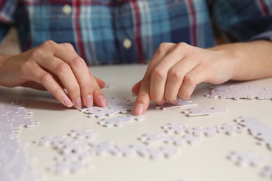 Young woman playing with puzzles at table, closeup