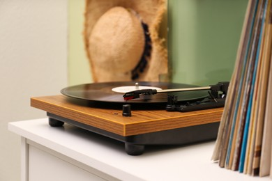 Turntable with vinyl record on white table indoors, space for text