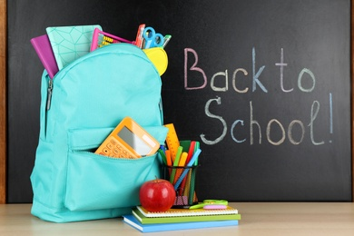 Bright backpack with school stationery on brown wooden table near black chalkboard. Back to School
