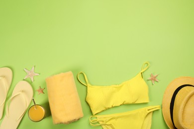 Flat lay composition with beach objects on green background, space for text