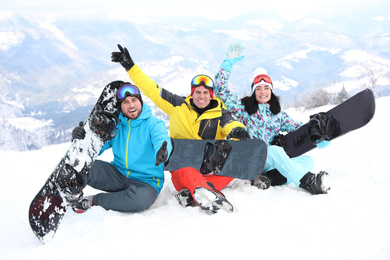 Friends with snowboards at mountain resort. Winter vacation