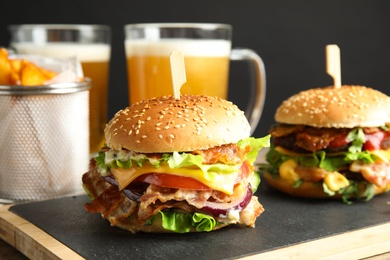 Tasty burgers with bacon served on board