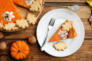 Delicious homemade pumpkin pie on wooden table, flat lay