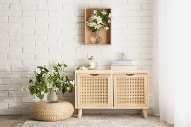 Beautiful jasmine flowers and wooden commode in room