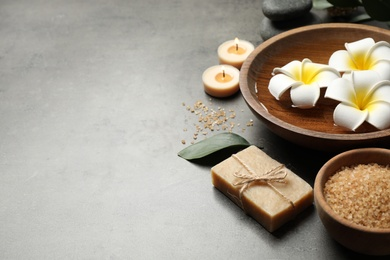 Spa composition with soap and spa items on grey table, space for text