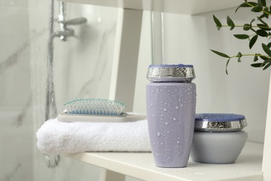 Hair care cosmetic products, towel and brush on white shelf indoors