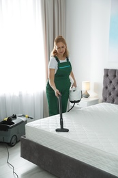 Janitor cleaning mattress with professional equipment in bedroom