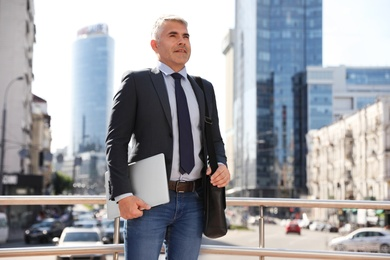 Portrait of handsome businessman with laptop in city, space for text